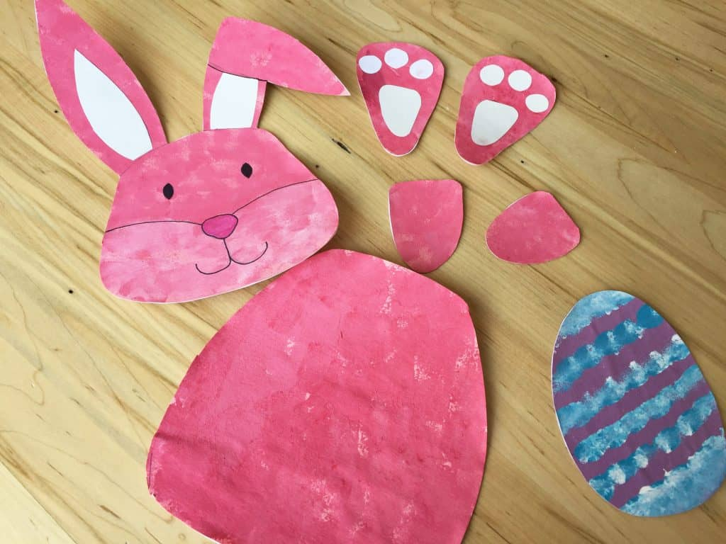 Cut out pieces of the bunny craft template on the table.